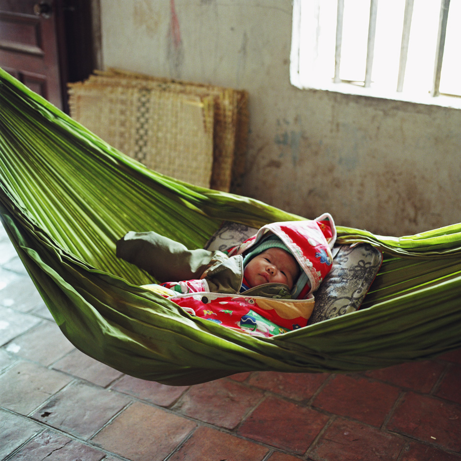 Vietnam - Craft villages - A two month old baby boy asleep in a hammock in Tang Tien a bamboo basket weaving village